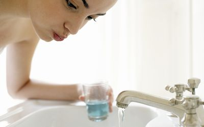 Young woman rinsing mouth, leaning over sink, close-up