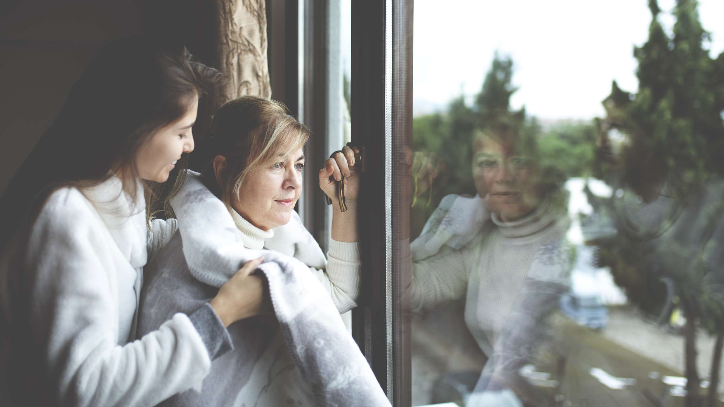 Young woman wrapping up an older woman at window