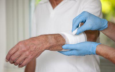 a nurse putting gauze wrap on an elderly patient's arm