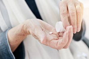 Wrinkled hands getting pill from container