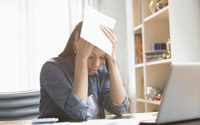 Anxious mixed race woman paying bills on laptop - stock photo