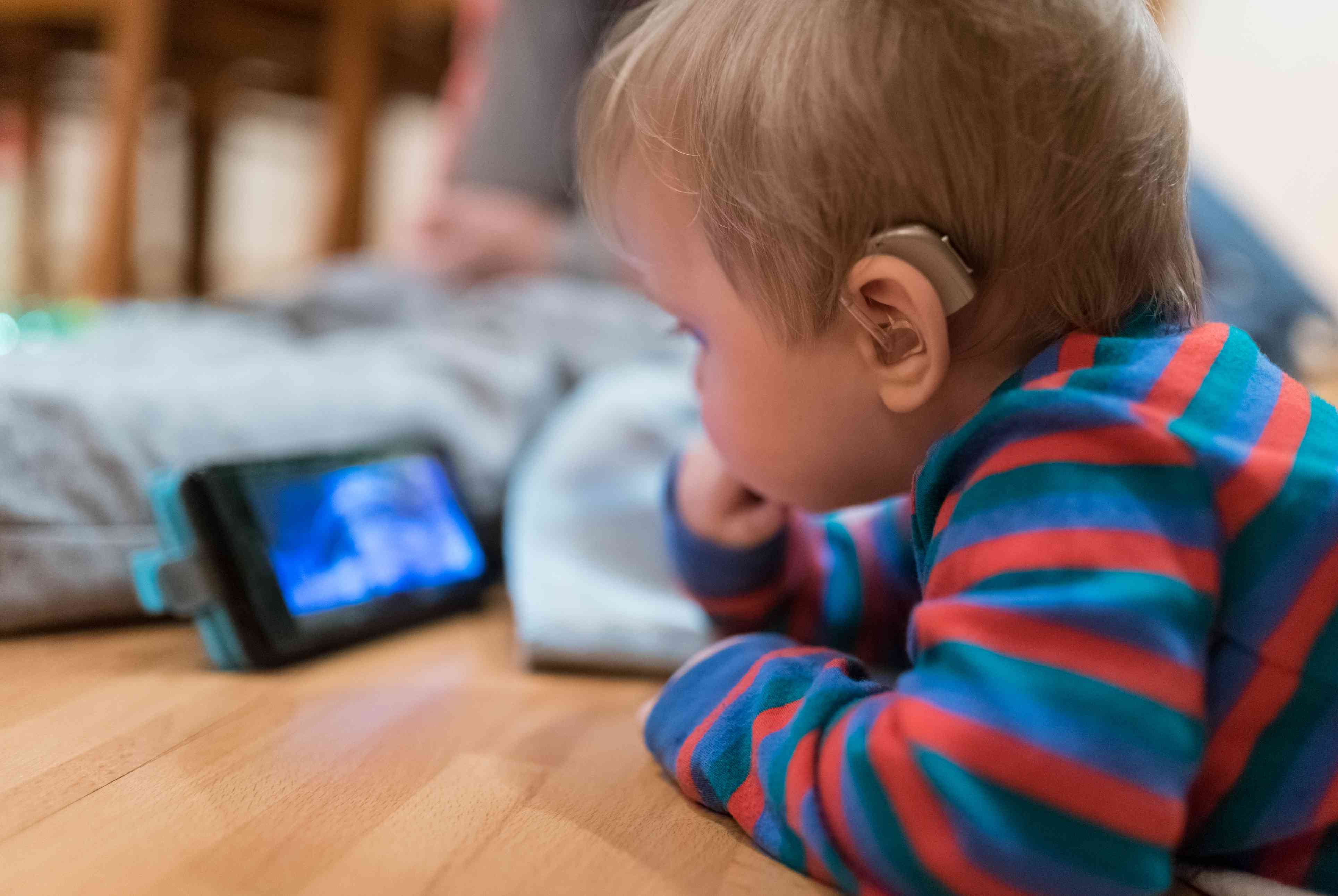 baby with a hearing aid playing with an ipad