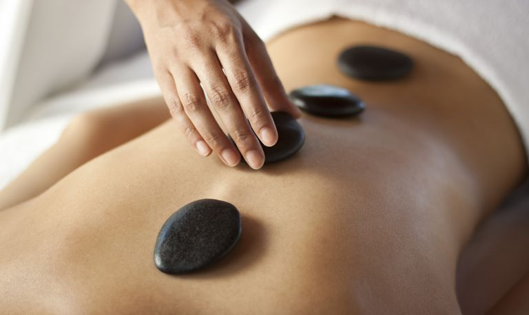 A person getting hot stone massage therapy