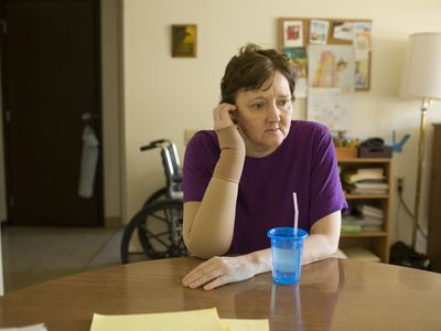 female hospice patient with anxiety sits at a table