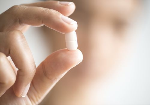 Close up of someone holding a pill