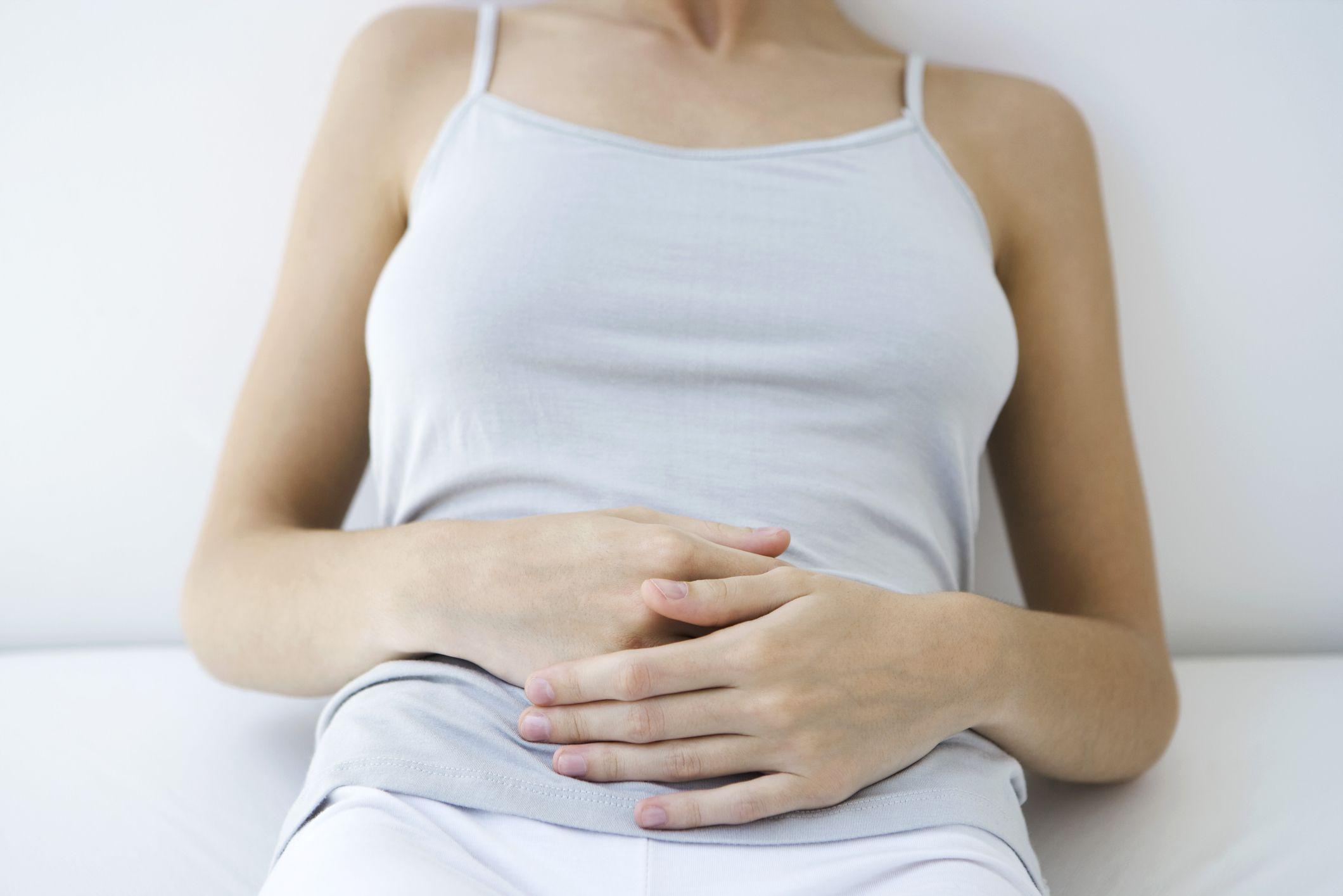 woman holding abdomen while sitting