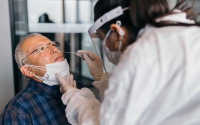 Older man receiving a COVID test.
