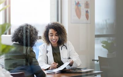 Smiling female doctor points out test results to unrecognizable woman - stock photo