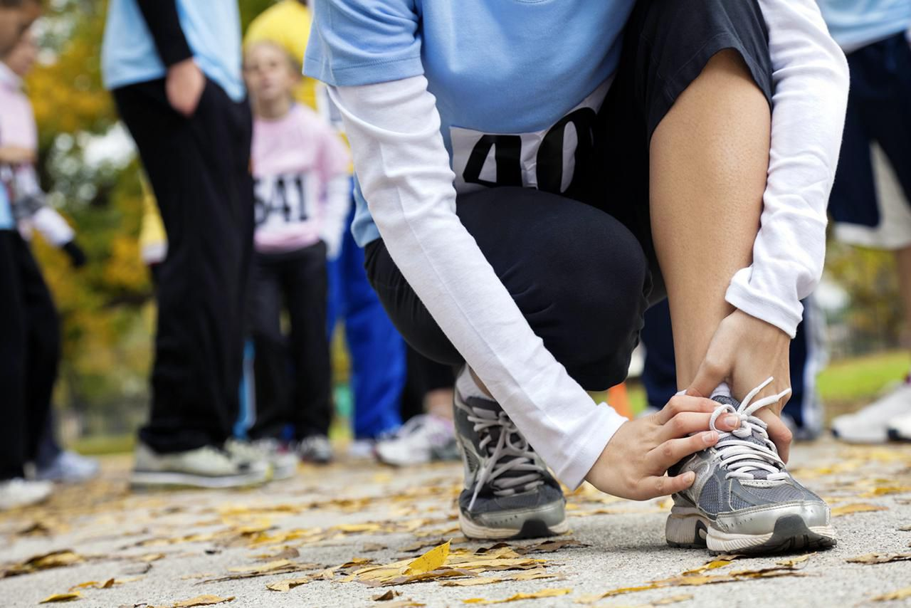 Woman holding her sprained ankle at a race