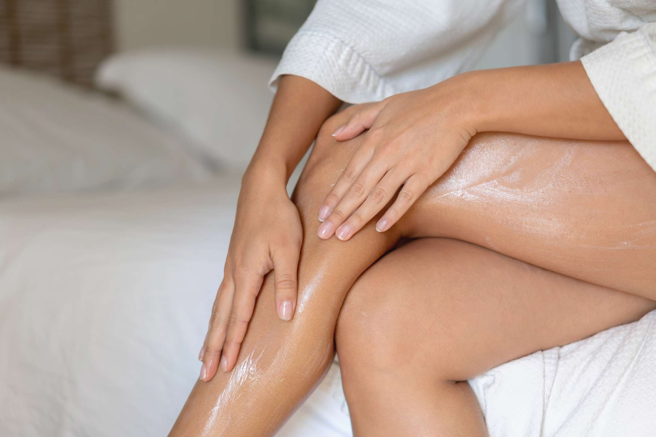 Woman applying lotion to her bare legs