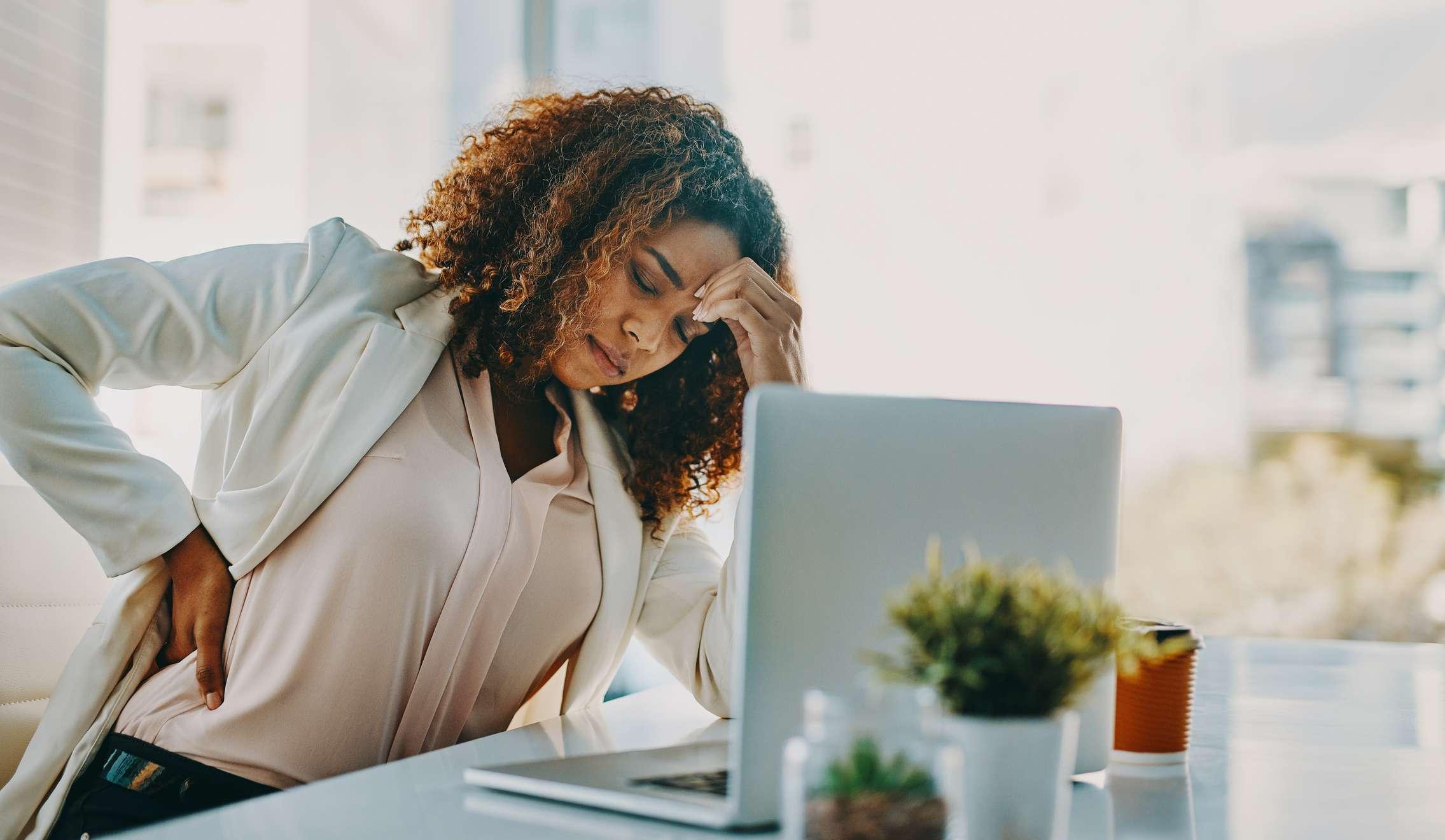women holding lower back in pain