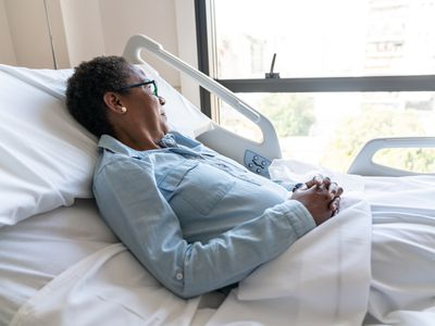 Pensive adult black patient looking away to the window while lying down on hospital bed
