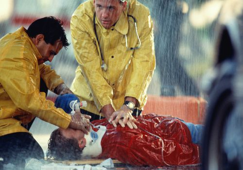 Paramedic performing CPR in the rain