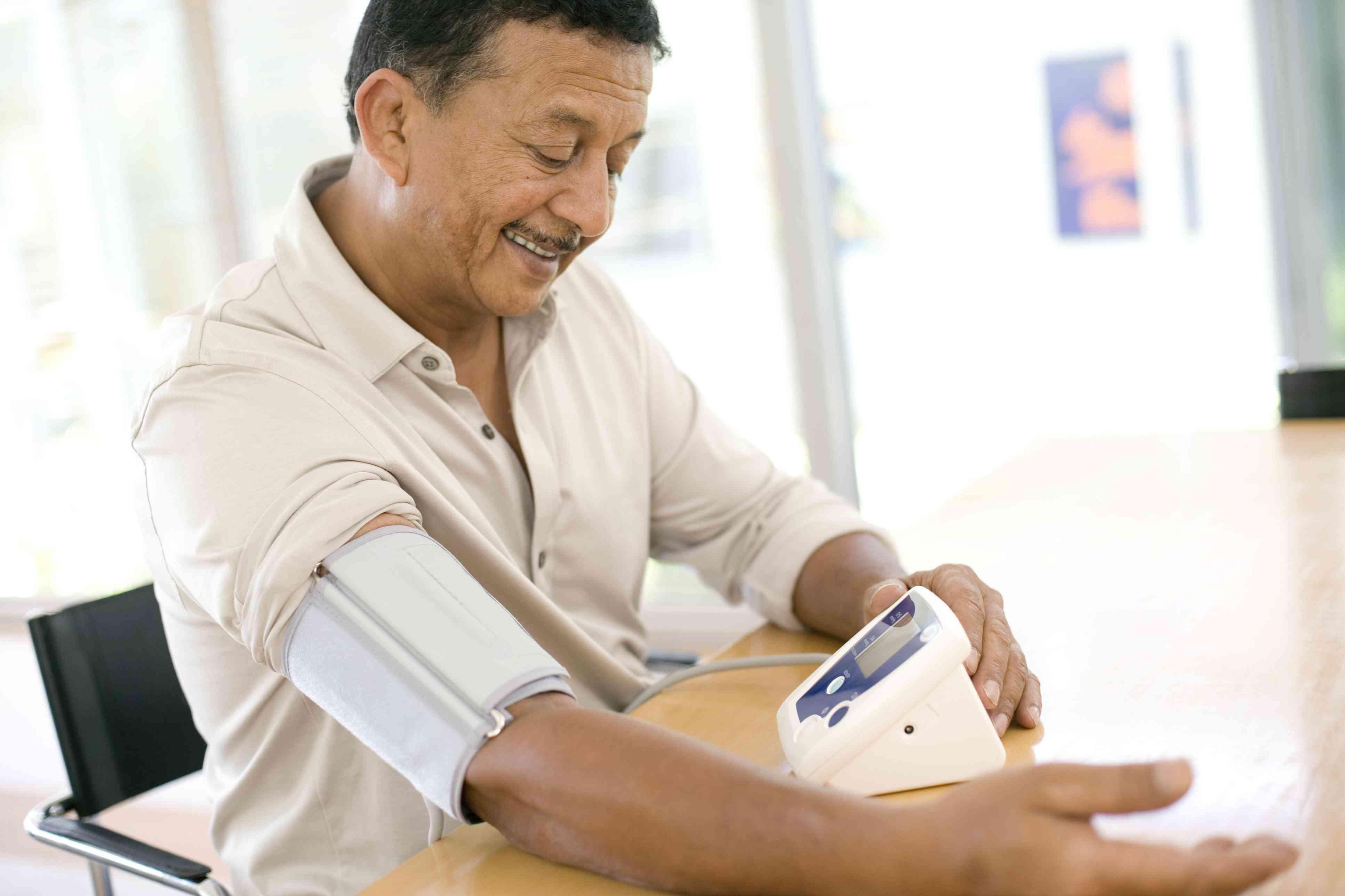 A man checks his blood pressure at home