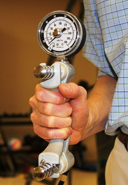 A handgrip dynamometer is used to accurately measure grip strength.