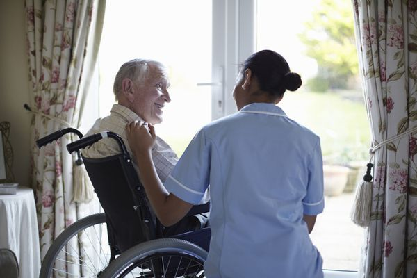 Nurse talking to older man in home