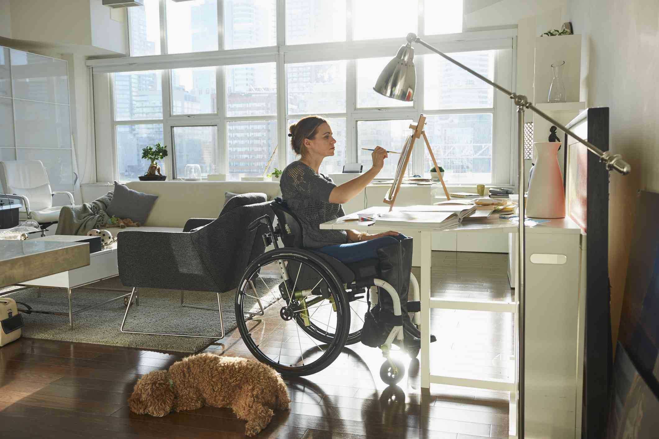 Caucasian woman in wheelchair painting on easel - stock photo