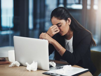 Shot of a young businesswoman suffering with a headache while working in an office