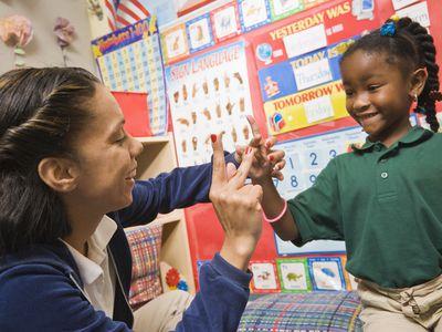Teacher showing pre-school girl sign language