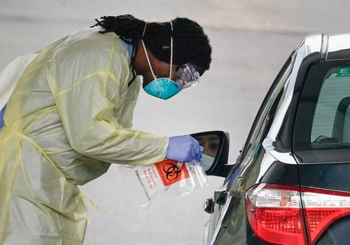 A healthcare worker screens a patient for COVID-19 at a drive through coronavirus testing site.