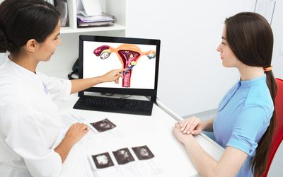 Gynecology, consultation. Gynecologist explains to a woman about a disease of the uterus