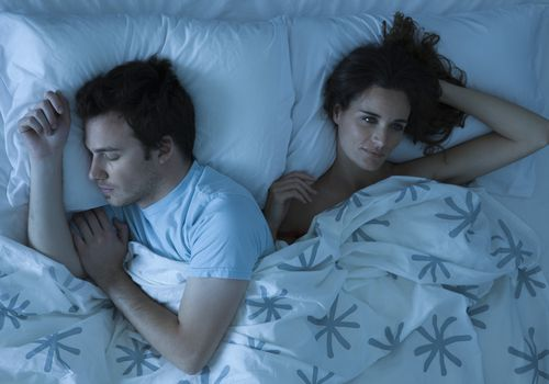 Woman awake in bed next to a sleeping man