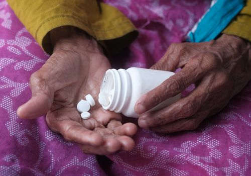 ElElderly woman pouring pills from bottle on hand, closeup view