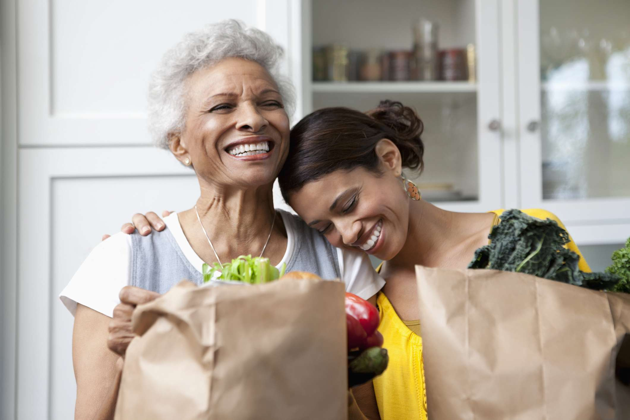 Mother and adult daughter unloading grocery bags