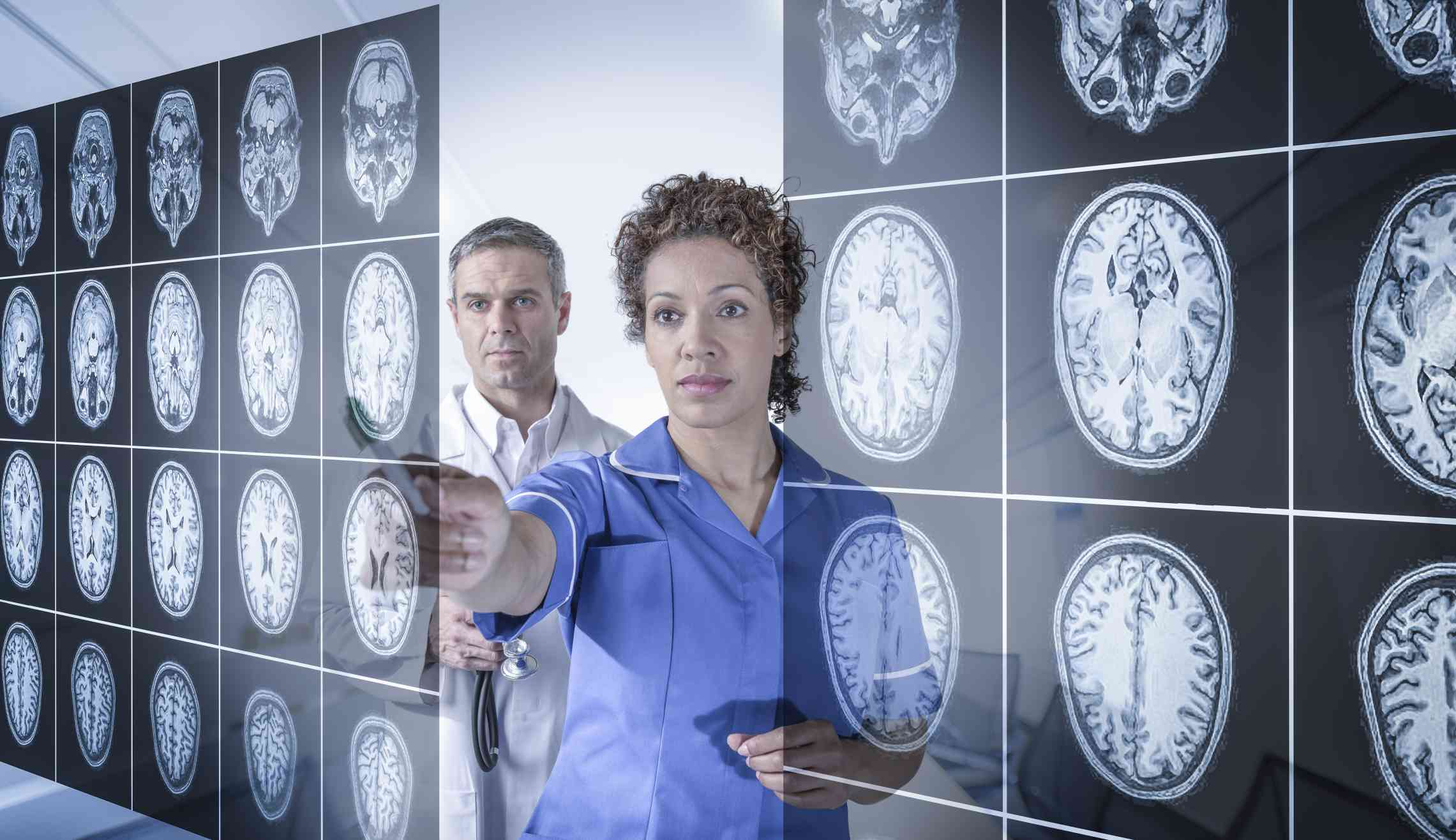 Two doctors studying images of the brain