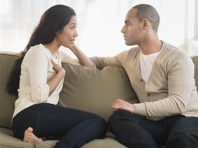 young couple facing each other on couch and having a discussion