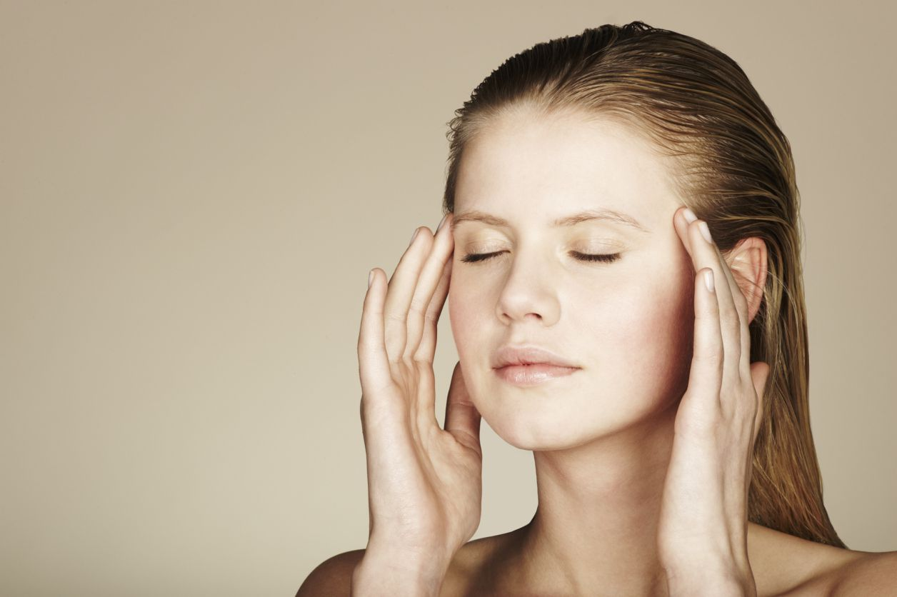 Young woman massaging her temples with her eyes closed standing against a beige background