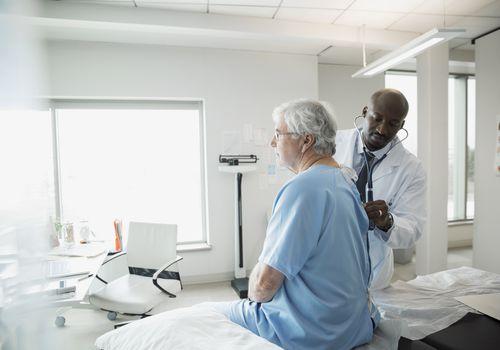 Doctor checking senior mans back in examination room
