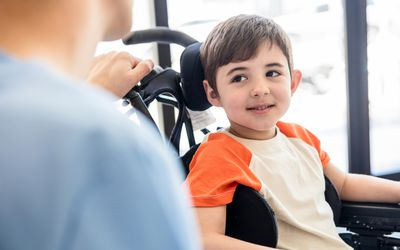 Beautiful little boy on wheelchair smiling and looking with admiration at his unrecongizable physical therapist
