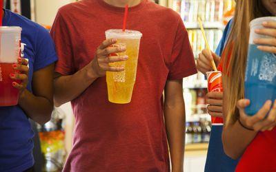 Three teenagers drinking soft drinks