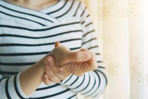 woman touching painful wrist