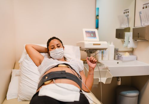 Pregnant woman on hospital bed wearing mask with monitoring belly band
