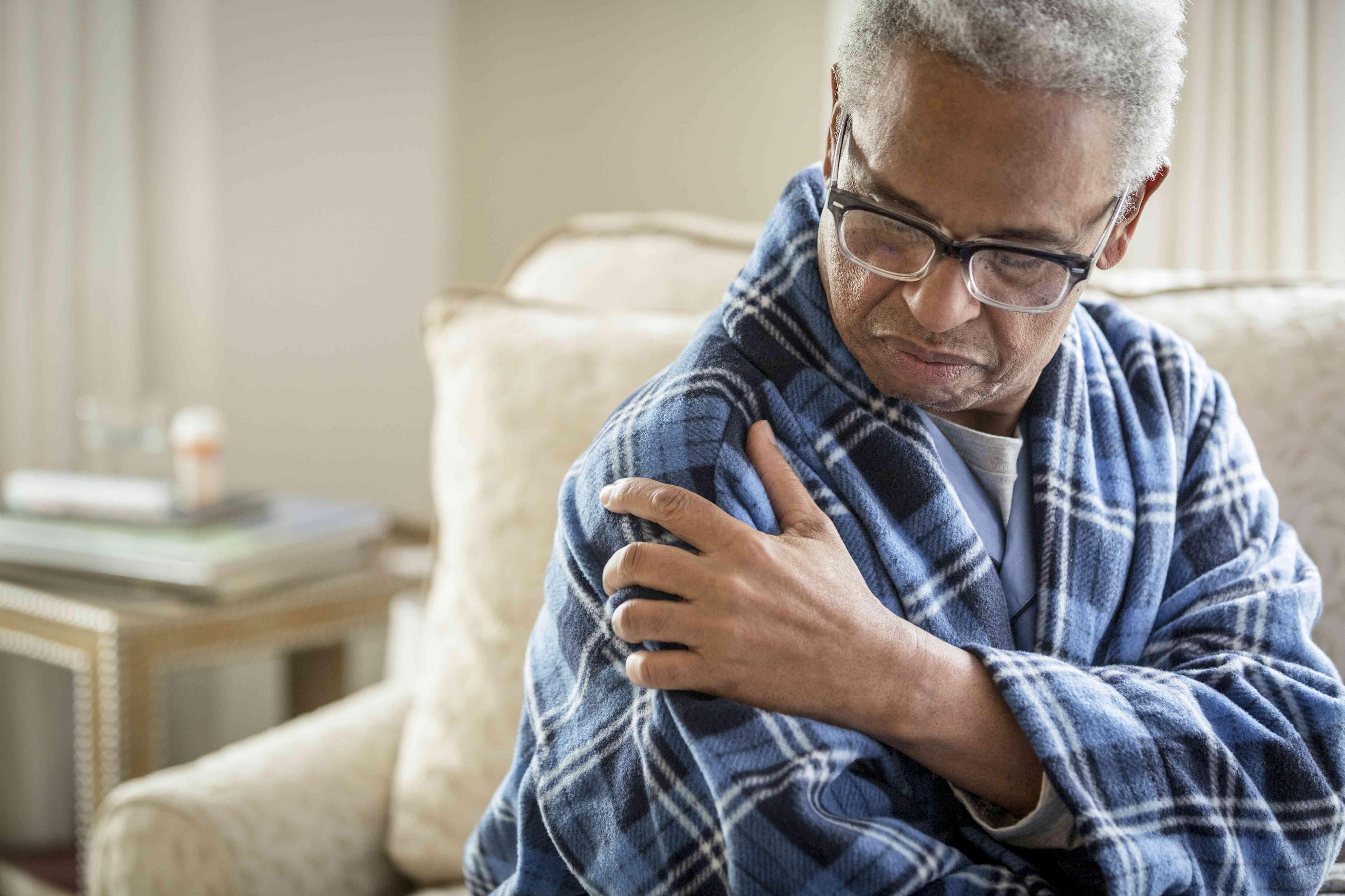 Senior man with arthritis rubbing his shoulder