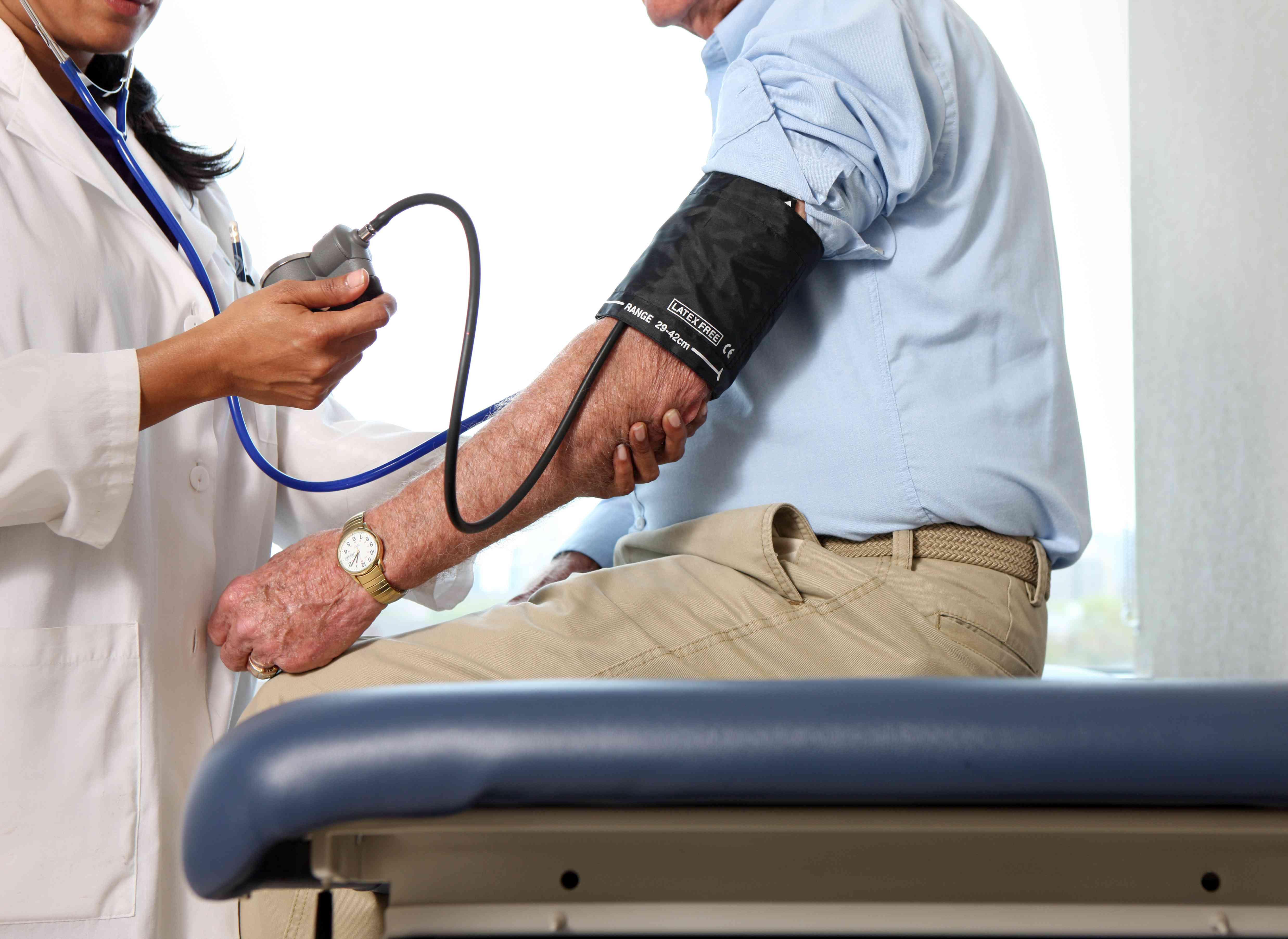 Doctor checks man's blood pressure.