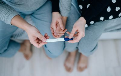 Couple holding a pregnancy test.