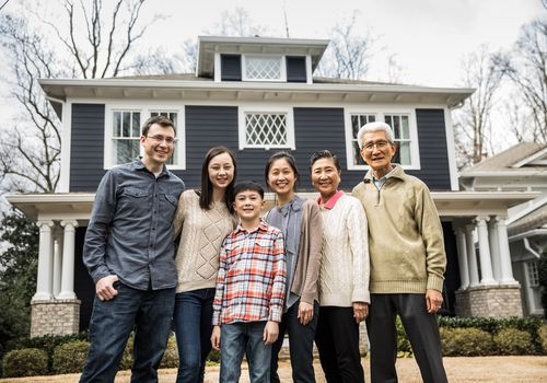 Several generations of a multi-ethnic family stand in front of a house.