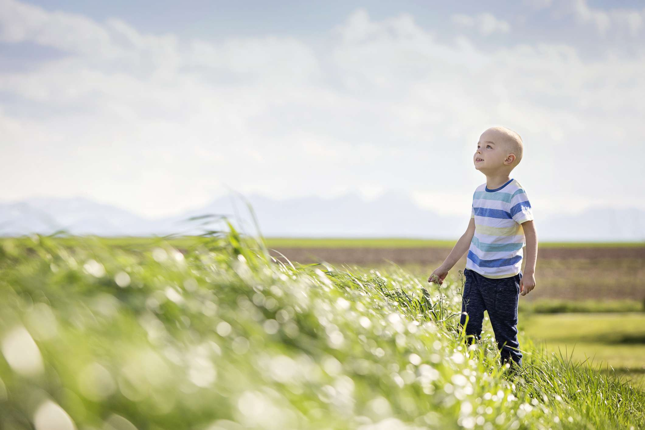 Child with Acute Lymphoblastic Leukemia standing in a field on a sunny day