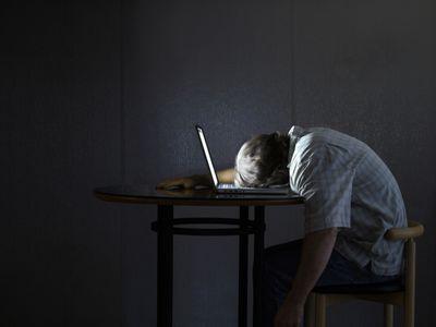 Man sleeping on the keyboard of his laptop