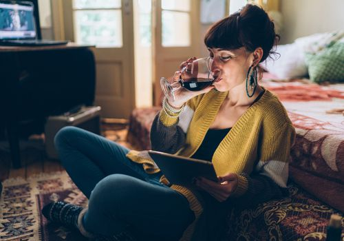 woman drinking wine looking at tablet