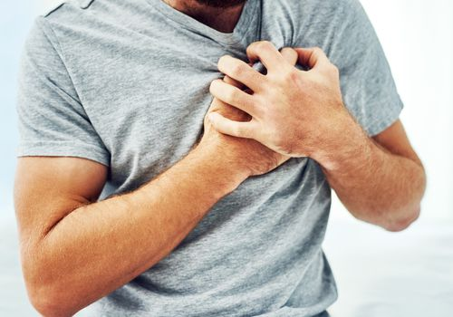 Close up of man wearing gray tee shirt clutching his chest like he's having chest pain