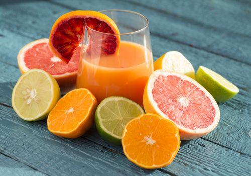 Citrus fruit surrounding a glass of fruit juice