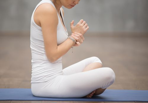 Young woman sitting on a yoga mat rubbing her wrist
