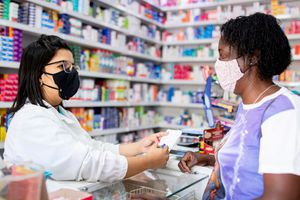 Pharmacist working in a pharmacy, using face mask