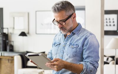 Caucasian man using digital tablet in livingroom