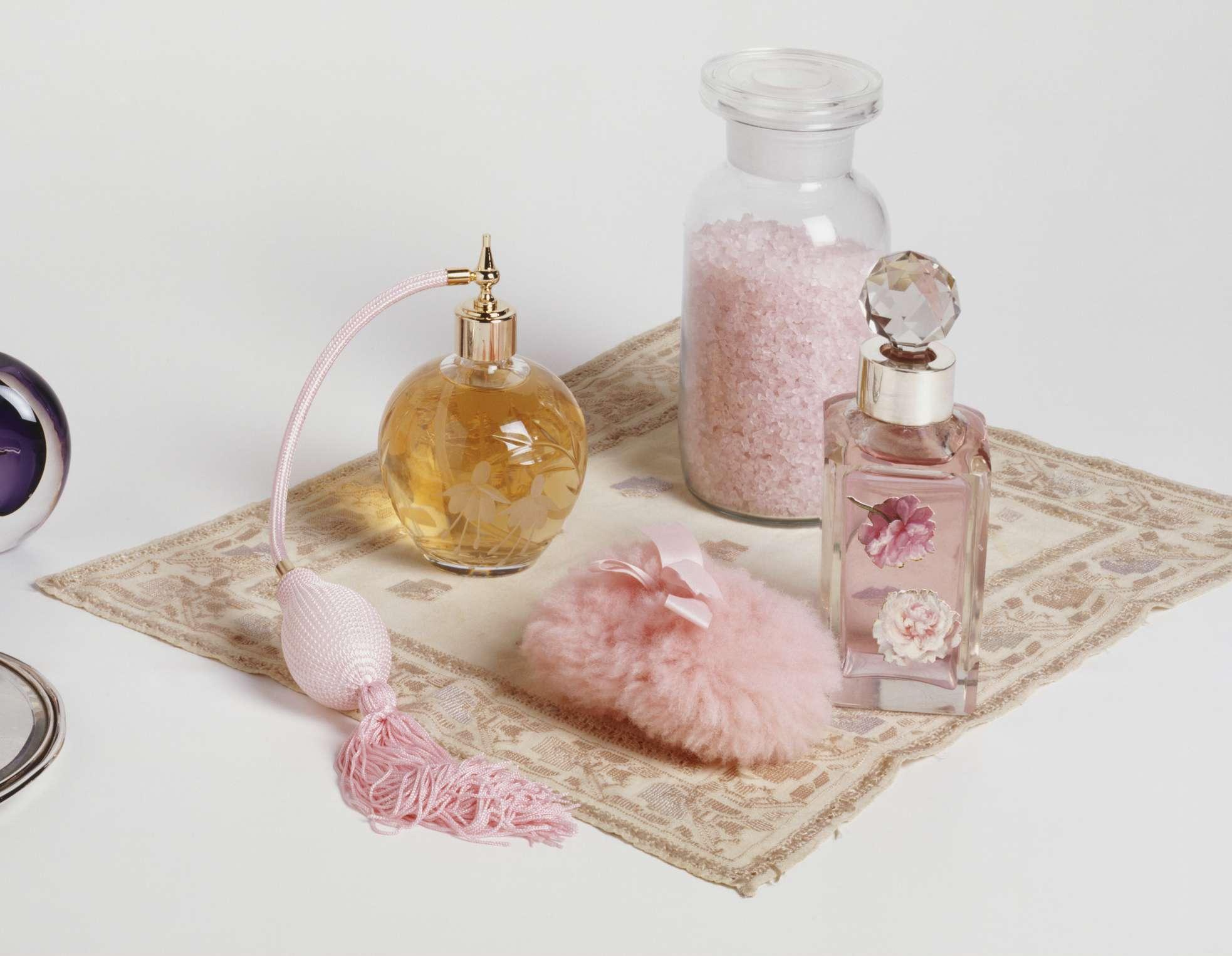 Perfume and bathsalts sit on a cloth.