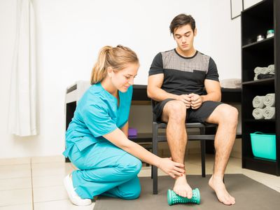 Physiotherapist Treating Plantar Fasciitis In Athlete